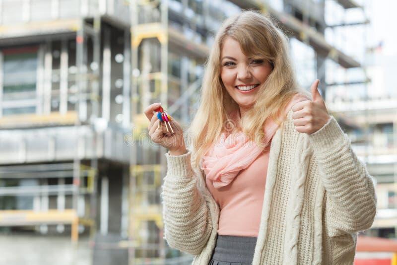 Mujer con llaves en frente de la construcción de nueva viviendas fotografía de archivo libre de regalías