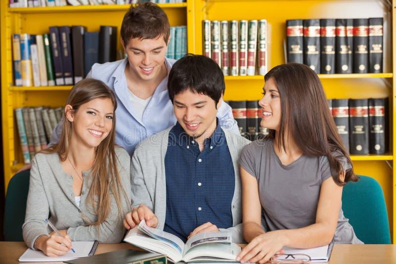 Mujer con los amigos que estudian en biblioteca de universidad foto de archivo