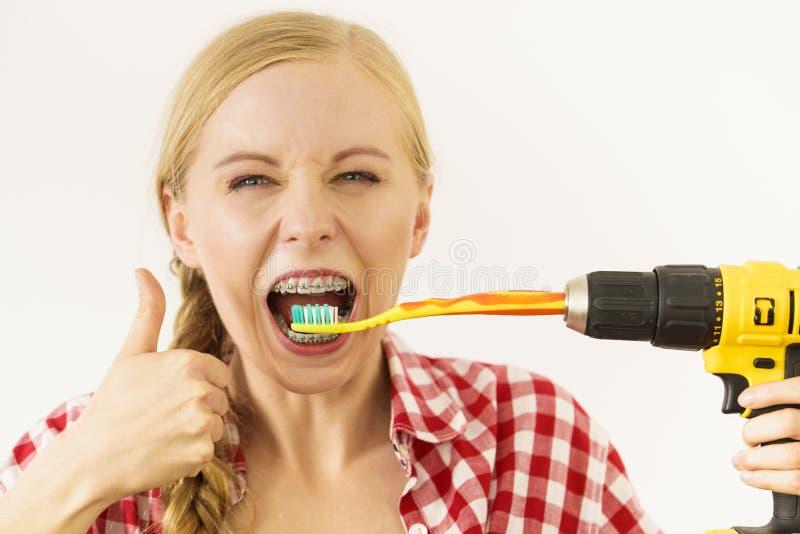 Mujer con los apoyos que cepillan los dientes con el taladro fotos de archivo