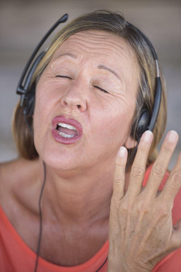 Mujer con los auriculares que canta imagen de archivo