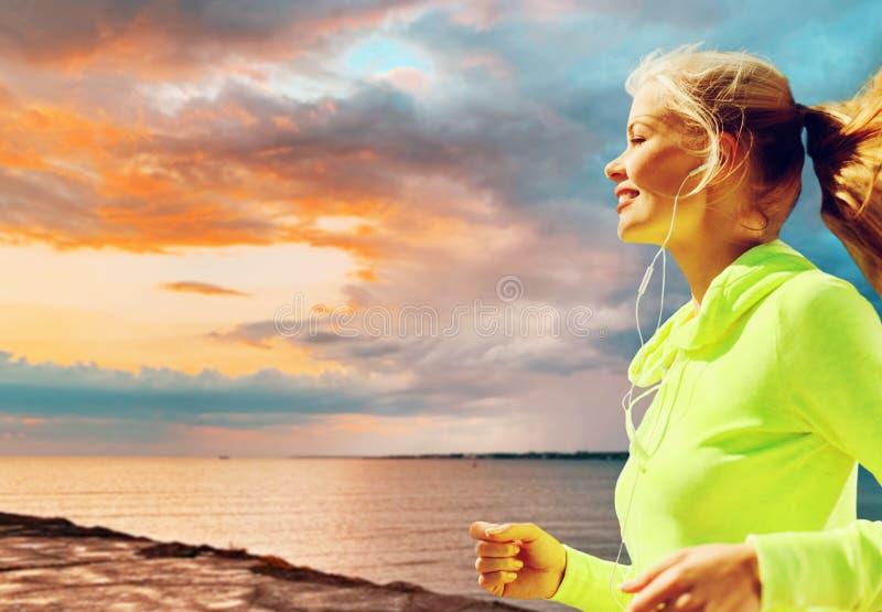 Mujer con los auriculares que corren sobre puesta del sol del mar fotos de archivo