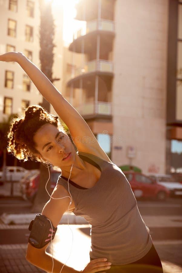 Mujer con los auriculares que hacen cierto estirar fotografía de archivo libre de regalías