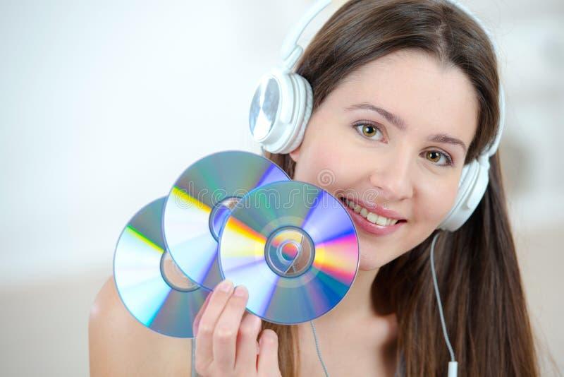 Mujer con los auriculares que sostienen los Cdes foto de archivo