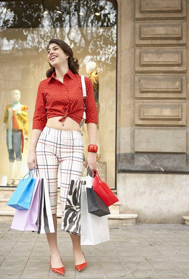 Mujer con los bolsos de compras que sonríe en el almacén fotografía de archivo libre de regalías