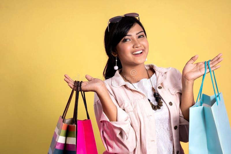 Mujer con los bolsos de compras sobre fondo amarillo fotografía de archivo