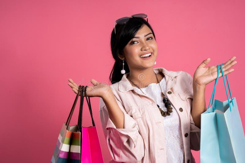 Mujer con los bolsos de compras sobre fondo rosado imagenes de archivo