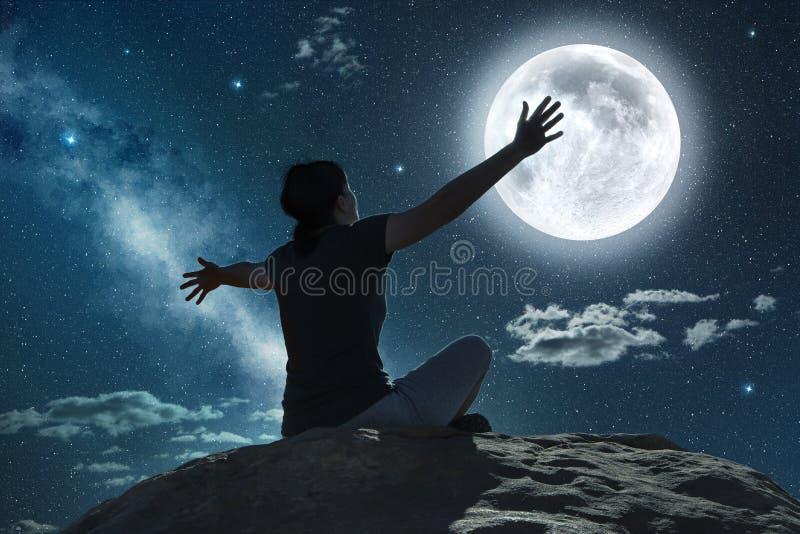Mujer con los brazos aumentados delante de la luna imagen de archivo