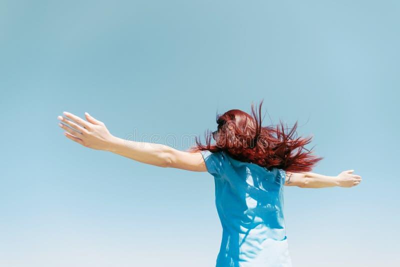 Mujer con los brazos aumentados en fondo del cielo azul foto de archivo