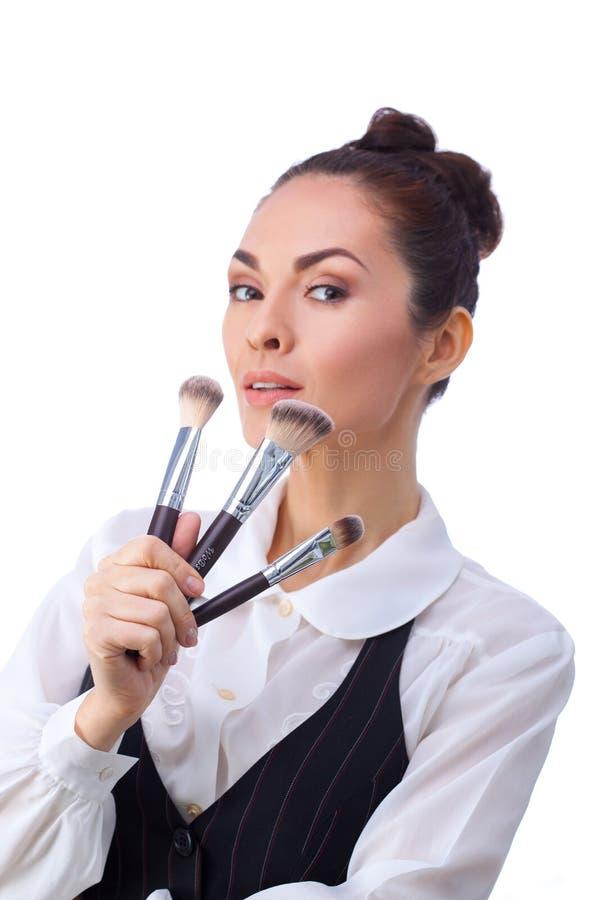 Mujer con los cepillos del maquillaje Todos aislados en blanco imagen de archivo