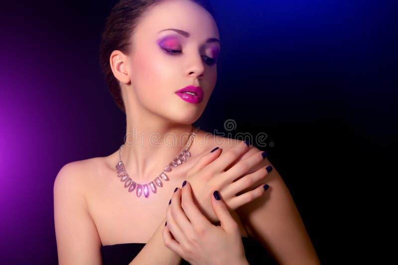 Mujer con los clavos azules y el maquillaje creativo imagen de archivo