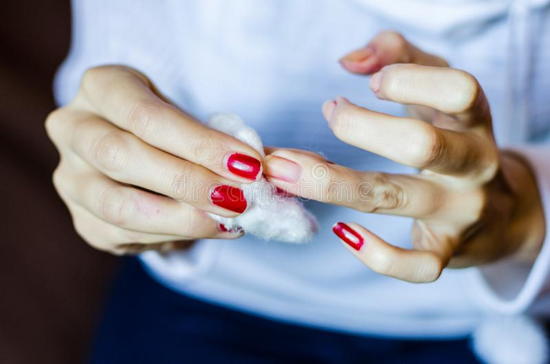 Mujer con los clavos rojos largos que quitan al esmalte de uñas fotos de archivo
