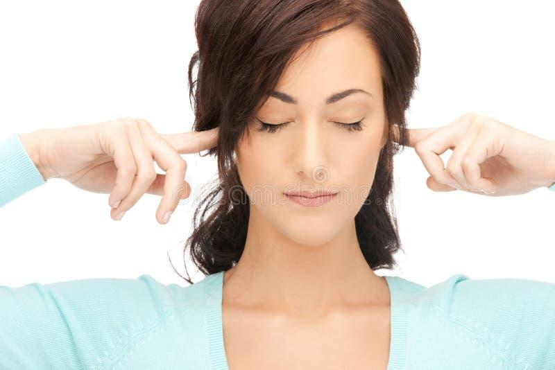 Mujer con los dedos en oídos imagen de archivo