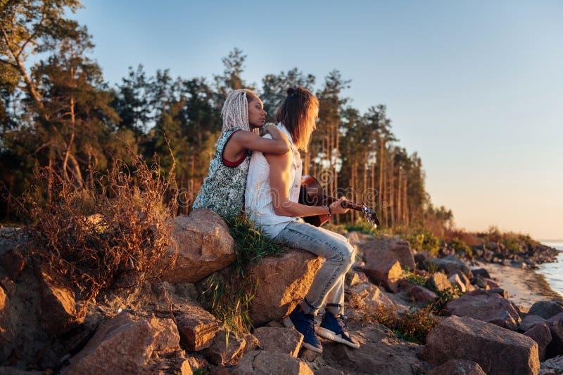 Mujer con los dreadlocks blancos que abrazan la sentada del novio en rocas con la guitarra imagen de archivo