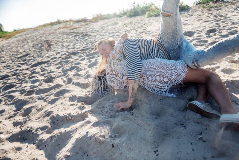 Mujer con los dreadlocks blancos que abrazan a su novio hermoso que miente en la arena imagen de archivo libre de regalías