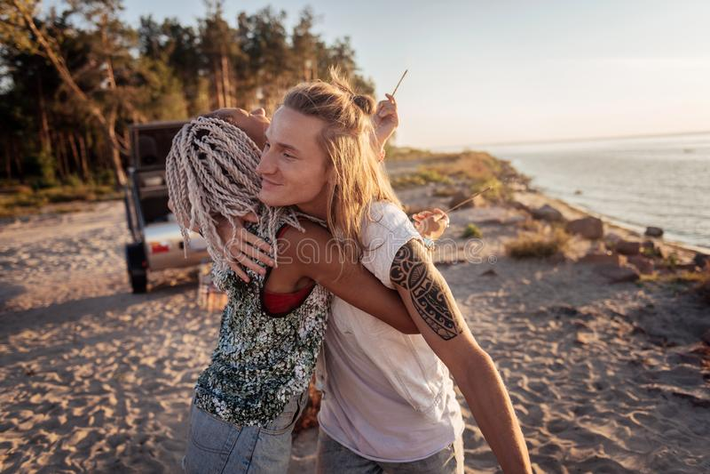 Mujer con los dreadlocks blancos que abrazan su sensación hermosa del hombre agradecida imagen de archivo libre de regalías