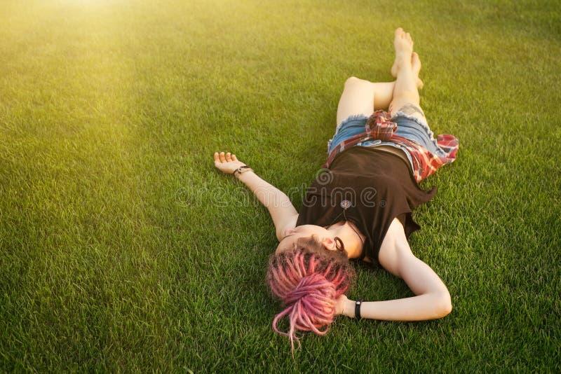 Mujer con los dreadlocks rosados que descansan sobre la hierba fotografía de archivo libre de regalías