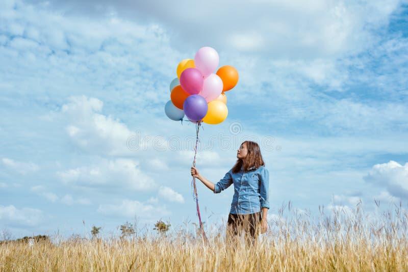 Mujer con los globos coloridos en el prado imagen de archivo libre de regalías