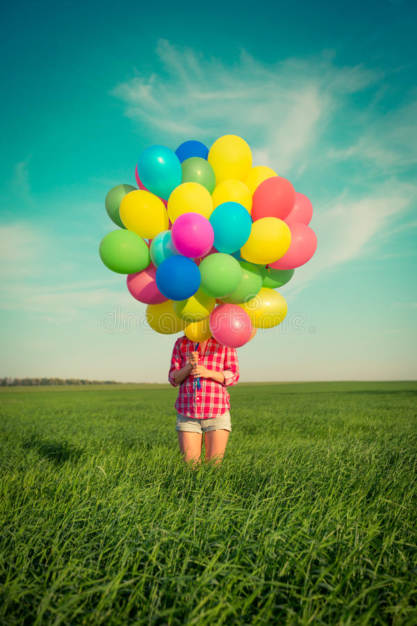 Mujer con los globos del juguete en campo de la primavera fotografía de archivo libre de regalías