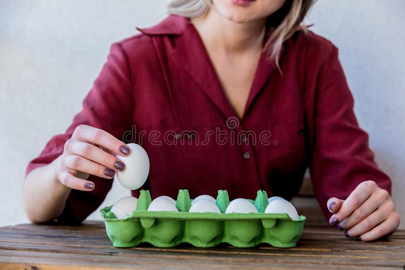 Mujer con los huevos del pollo en caja en una tabla de madera foto de archivo