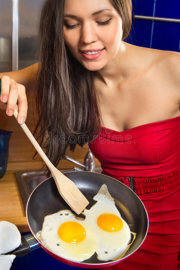 Mujer con los huevos revueltos imagenes de archivo