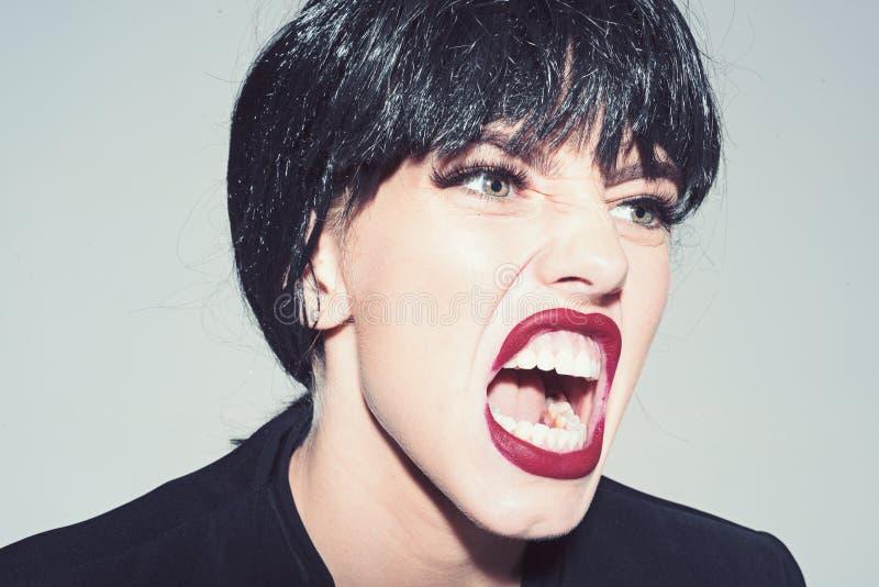 Mujer con los labios rojos atractivos que grita, cierre para arriba Concepto enojado del jefe La muchacha en cara de grito escand foto de archivo libre de regalías