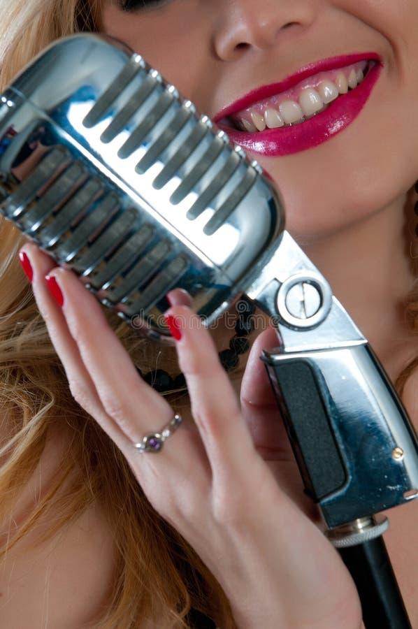 Mujer con los labios y el micrófono rojos