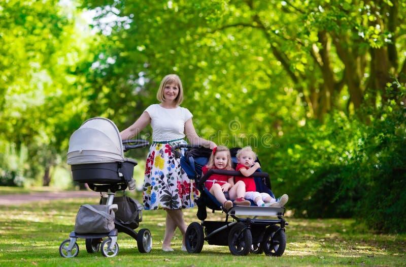 Mujer con los niños en cochecito en un parque fotografía de archivo