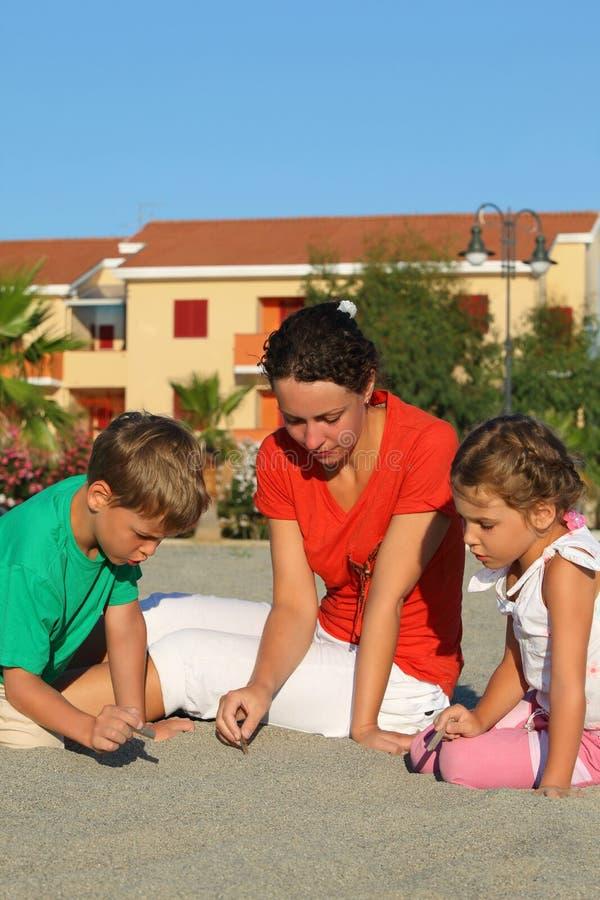 Mujer con los niños, la muchacha y el muchacho, drenaje en la arena imagen de archivo