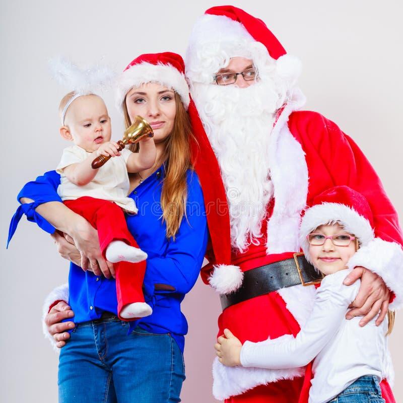 Mujer con los niños que se colocan con Papá Noel imagen de archivo