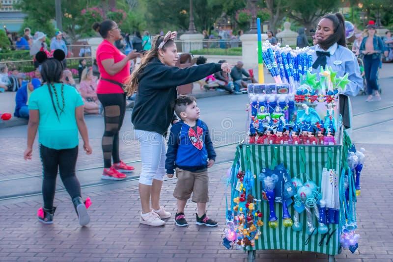 Mujer con los oídos de Minnies, comprando a su hijo un juguete de Disney en el reino mágico imagenes de archivo