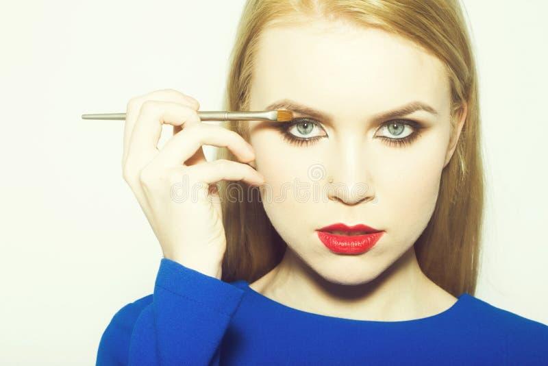 Mujer con los ojos azules que aplican sombras en los párpados fotos de archivo libres de regalías
