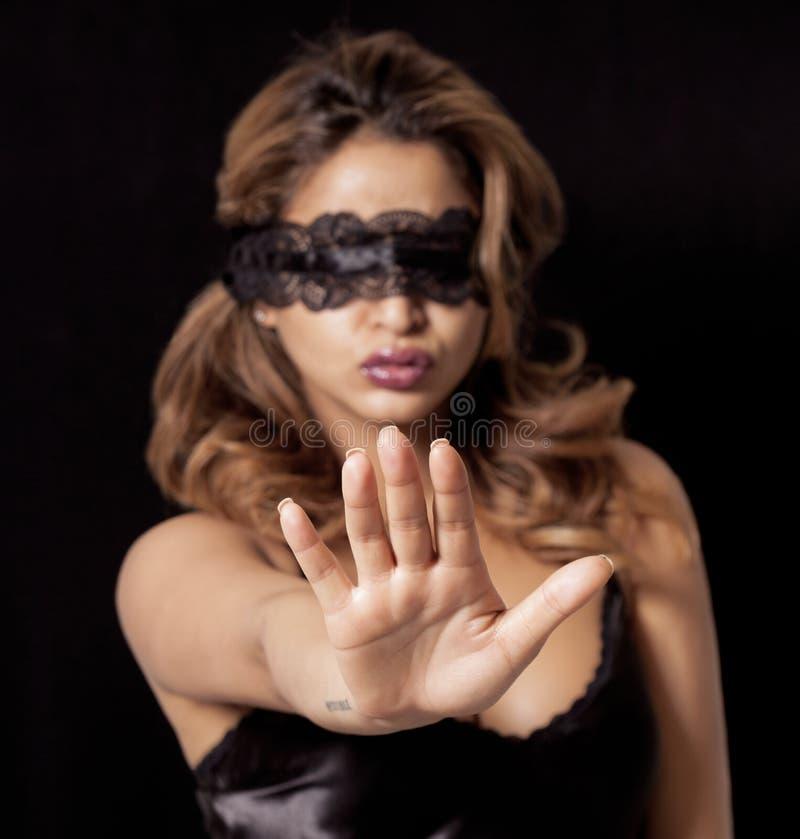 Mujer con los ojos vendados que hace gesto de la parada fotografía de archivo libre de regalías