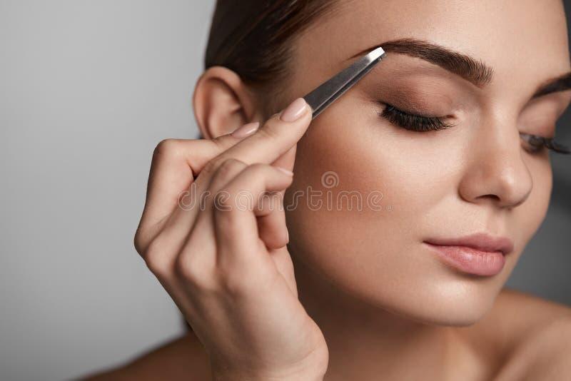 Mujer con los ojos y las pinzas cerrados para las cejas Herramientas de la belleza foto de archivo libre de regalías
