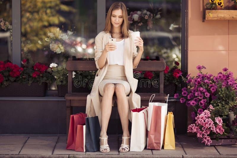 Mujer con los panieres que se sientan en banco foto de archivo libre de regalías