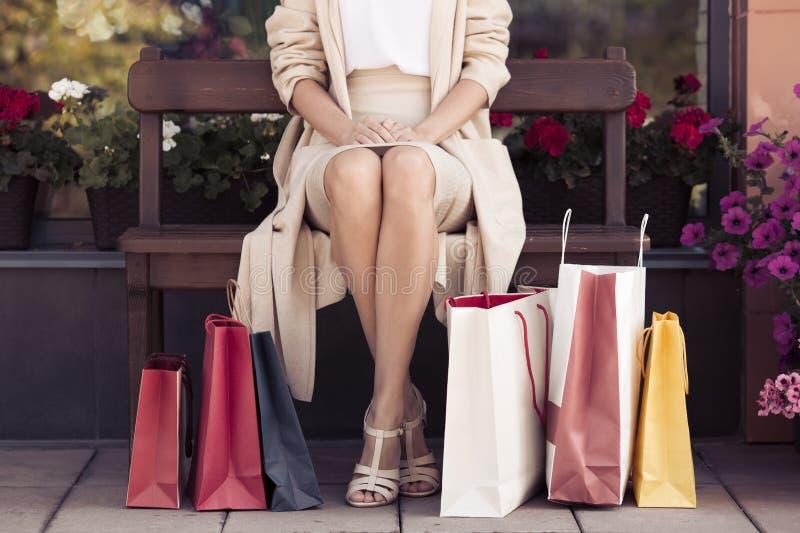 Mujer con los panieres que se sientan en banco Vida urbana y shopog foto de archivo libre de regalías