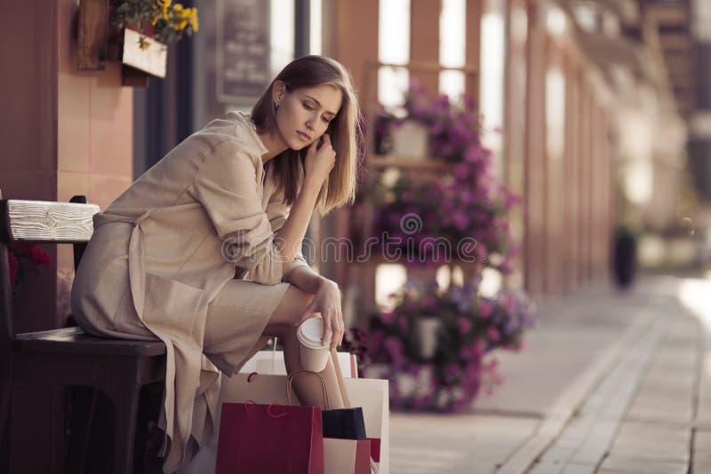 Mujer con los panieres que se sientan en banco Vida urbana y shopog imágenes de archivo libres de regalías