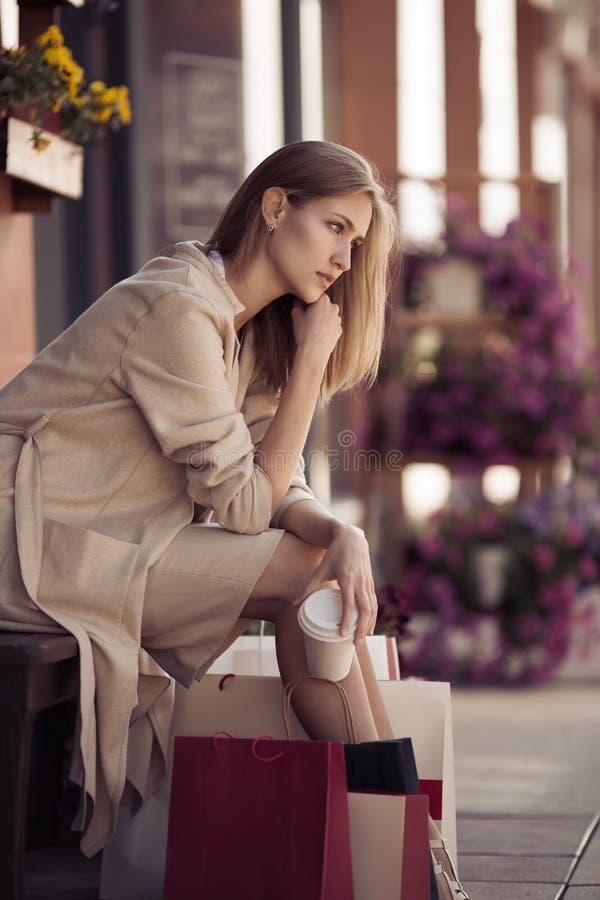 Mujer con los panieres que se sientan en banco Vida urbana y shopog fotografía de archivo libre de regalías