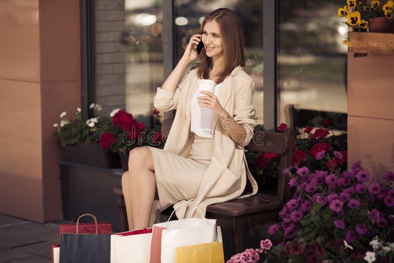 Mujer con los panieres que se sientan en banco y el teléfono que habla imagen de archivo libre de regalías