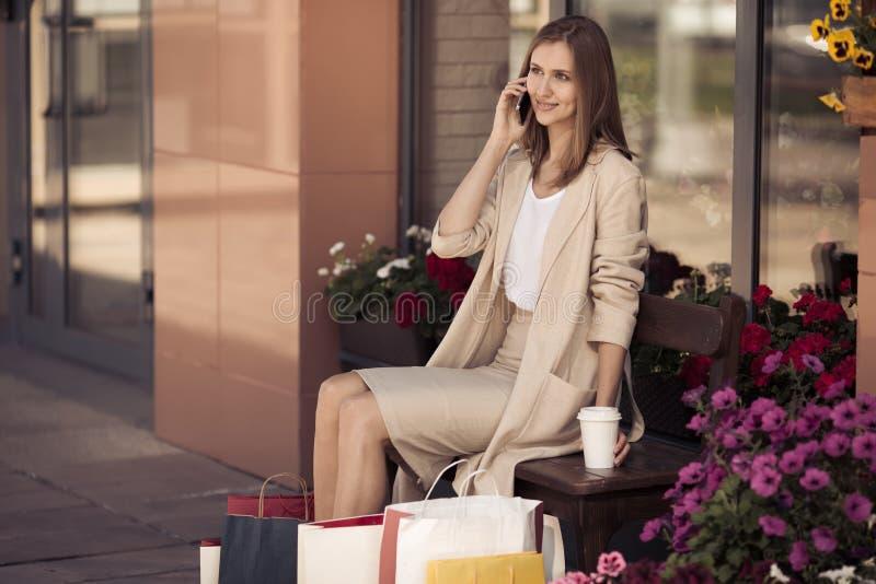 Mujer con los panieres que se sientan en banco y el teléfono que habla fotos de archivo libres de regalías