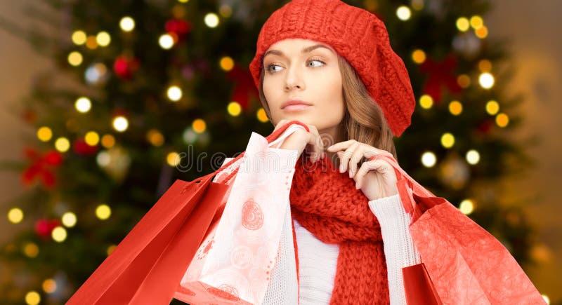 Mujer con los panieres sobre luces de la Navidad fotografía de archivo