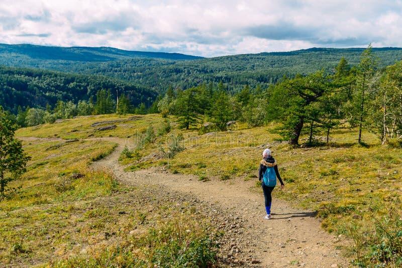 Mujer con los paseos de la mochila a lo largo del sendero con la montaña imagen de archivo libre de regalías