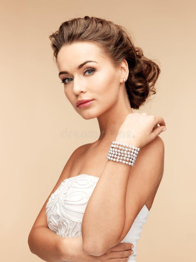 Mujer con los pendientes y la pulsera de la perla fotografía de archivo