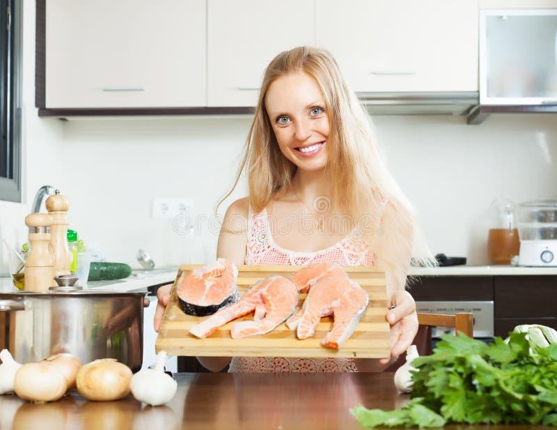Mujer con los pescados de color salmón crudos fotos de archivo libres de regalías