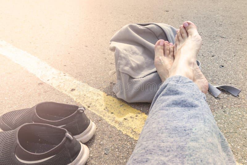 Mujer con los pies desnudos y mochila que se sienta en una carretera de asfalto con una sola línea amarilla vehículo que espera d imagenes de archivo