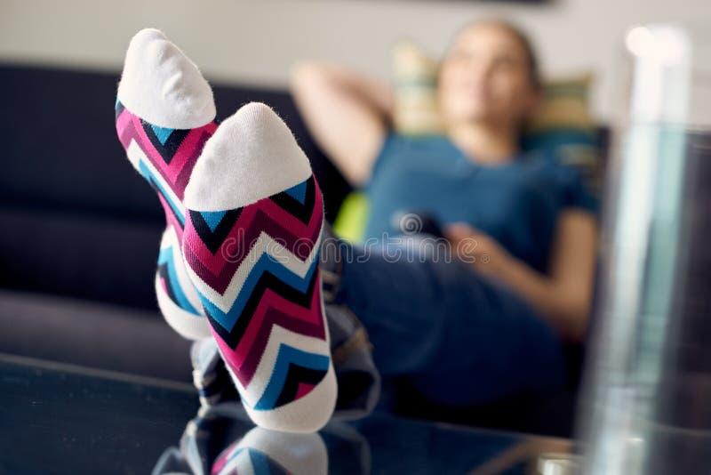 Mujer con los pies en la película de observación TV de la tabla en casa imagen de archivo