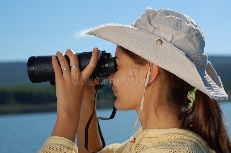 Mujer con los prismáticos sobre el cielo azul fotos de archivo libres de regalías