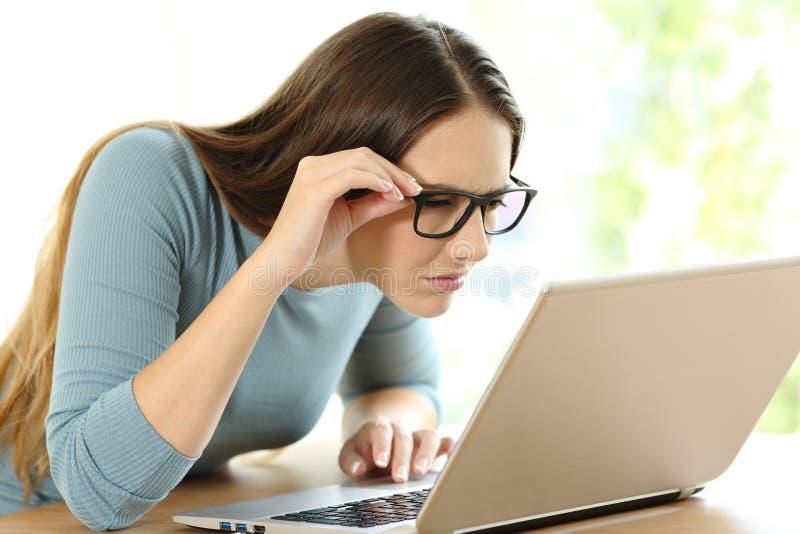 Mujer con los problemas de la vista a leer en la línea contenido imagen de archivo