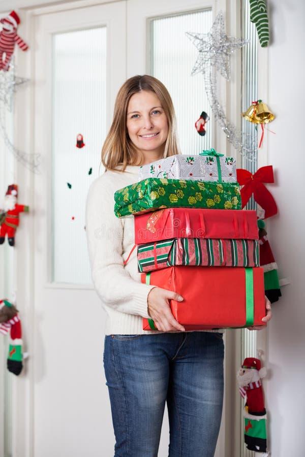 Mujer con los regalos que hacen una pausa la puerta durante la Navidad foto de archivo libre de regalías