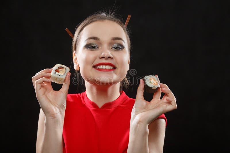 Mujer con los rollos de sushi fotos de archivo libres de regalías