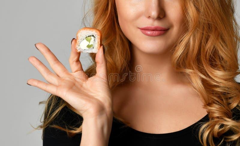 Mujer con los rollos de sushi del control de la muchacha del sushi en manos que sonríe en un gris claro fotos de archivo